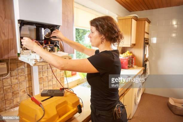 mujer fontanero reparar una caldera