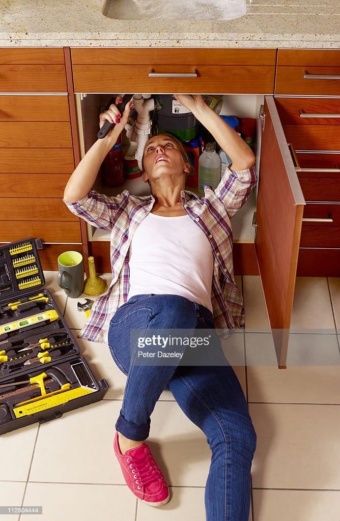 Female plumber under kitchen sink : Stock Photo