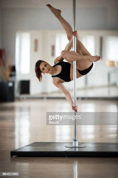Female pole dancer exercising in a dance studio.
