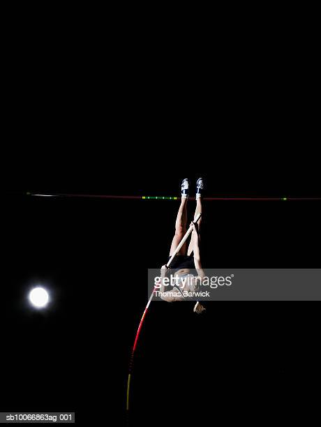 Female pole vaulter going over bar