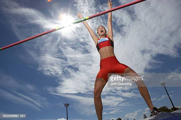 female pole vaulter landing on mat, arms raised, shouting - women's field event stock pictures, royalty-free photos & images