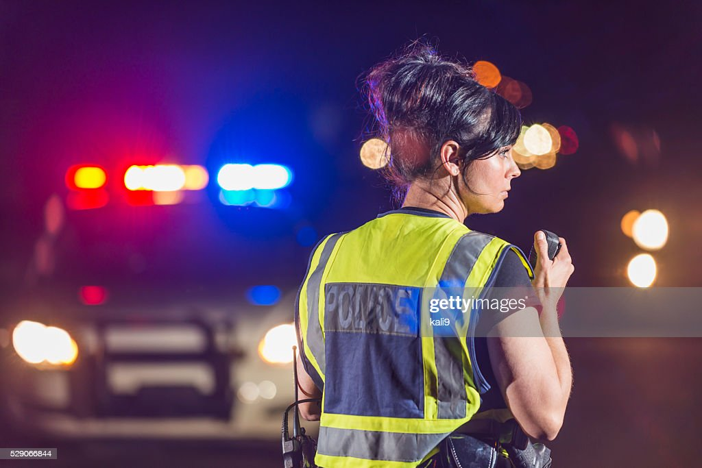 雌警察官夜に、ラジオで話している : ストックフォト