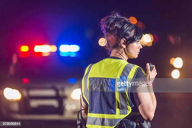 Weibliche Polizist bei Nacht, redet mit radio