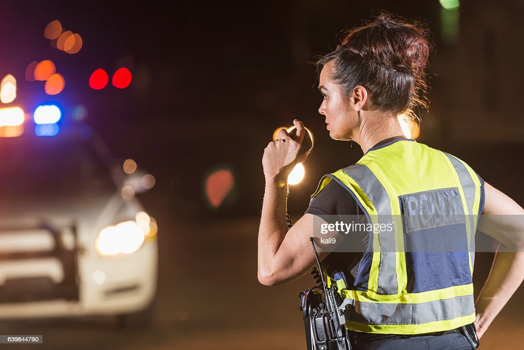 Female police officer at night, talking on radio : Stock Photo