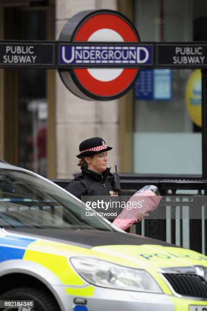 A female police officer carries flowers from a member of the public to the scene of last night's terrorist attack at London Bridge on June 4 2017 in...