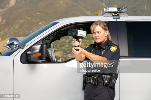 female police officer checking vehicle speed with radar
