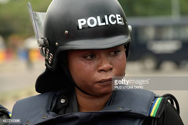 A female police officer faces supporters of 219 schoolgirls kidnapped by Boko Haram militants as police blocks the protesters from marching on the...