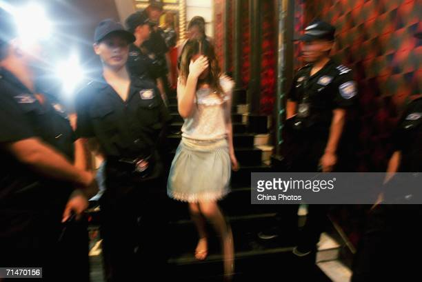 A female police officer leads away a woman during a police raid of an entertainment center which is suspected of being a front for a prostitution...
