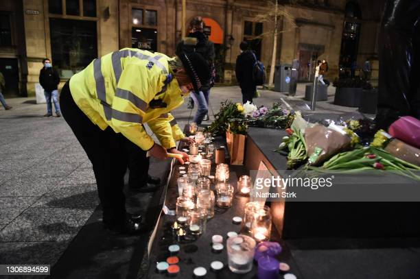 Female police officer lights a candle next to a makeshift memorial during a vigil for Sarah Everard, following her kidnap and murder, on Market...