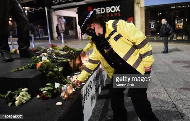 Female police officer lights a candle next to a makeshift memorial during a vigil for Sarah Everard, following her kidnap and murder, on March 13,...