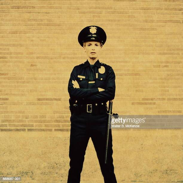 Female police officer standing against brick wall (paper negative)