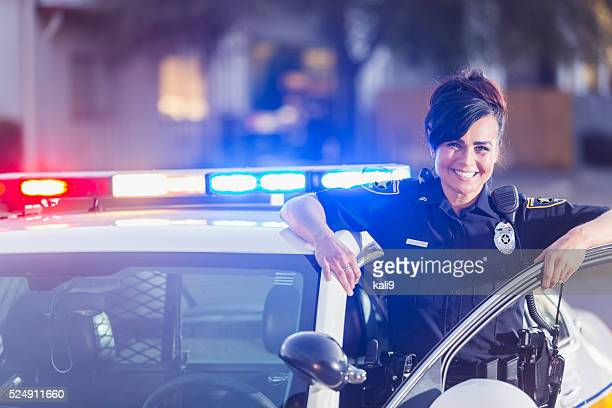 Female police officer standing next to patrol car