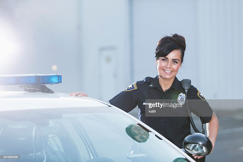 Female police officer standing next to patrol car : Stock Photo