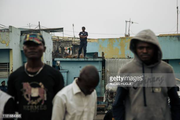Female police officer watches the convoy of the leader of the Democratic Republic of Congo's political party Movement for the Liberation of the Congo...
