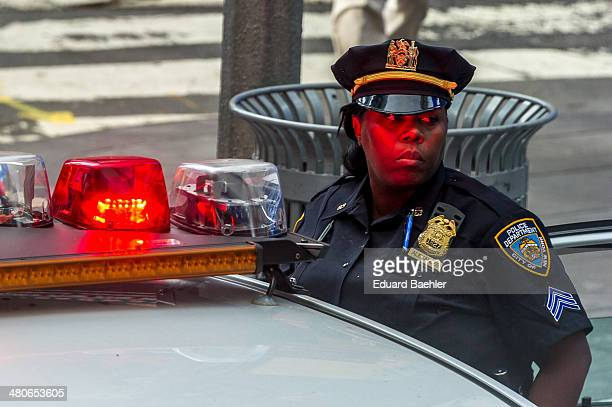 CONTENT] Female police officer with hat on observing the street backwards besides a police car with red emergency light glowing on her skin downtown...