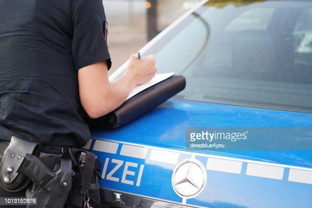 polizistin schreibt einen bericht über das verbrechen - polizei stock-fotos und bilder