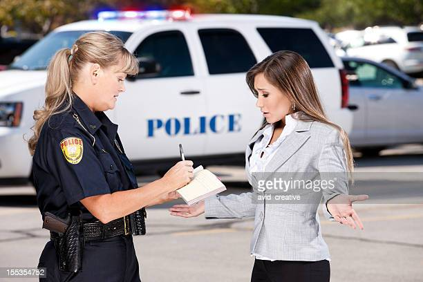 Female Police Officer Writing Citation to Businesswoman