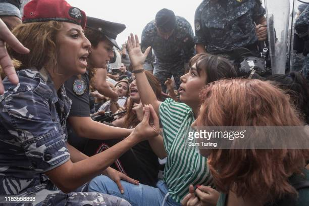 Female police officers negotiate with female demonstrators as police try to remove antigovernment protesters blocking a major highway in central...