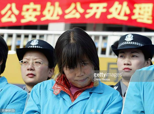 Female police officers stand behind convicted female criminals who are charged with illegally selling train tickets during a public sentence Januray...