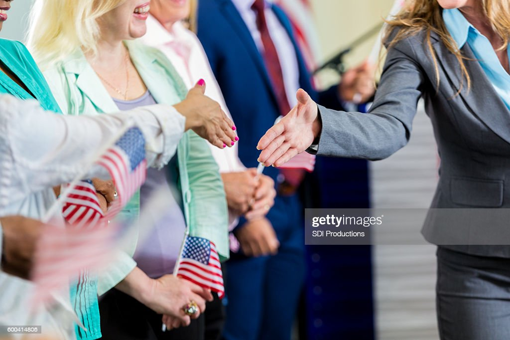 Female politician shaking hands with supporters at event : Stock Photo