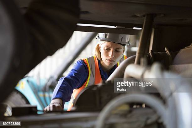 female port worker examining machinery in shipyard - dock worker stock photos and pictures