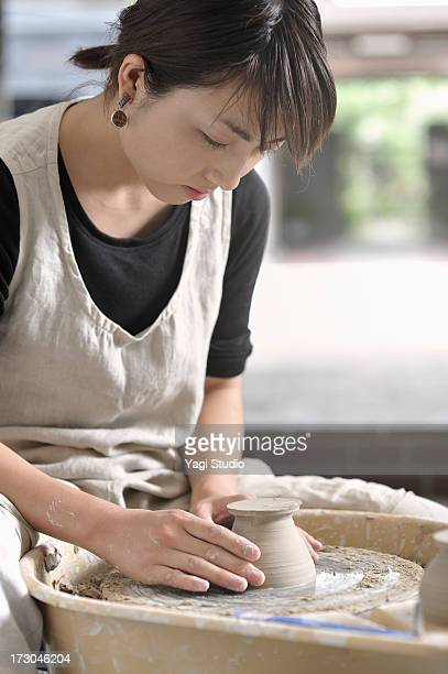 Female Potter are making a bowl in the studio