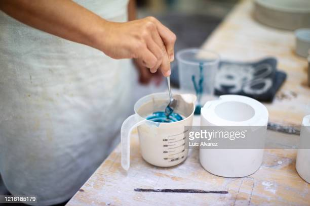 female potter making colorful ceramic pot in workshop - 染料 ストックフォトと画像