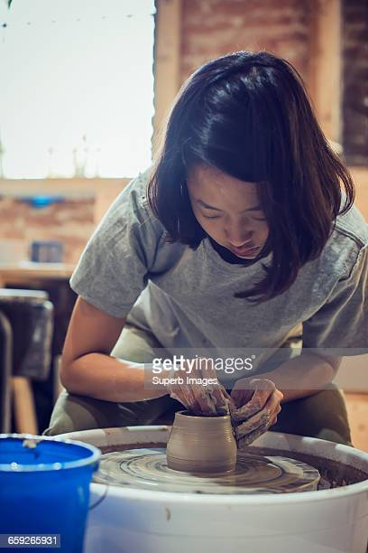 Female potter molding clay at pottery wheel