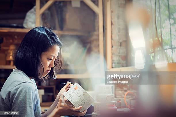 female potter paints clay pot in studio - tonkeramik stock-fotos und bilder