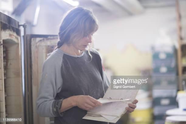 female potter reading notebook diary in workshop - sigrid gombert stock-fotos und bilder