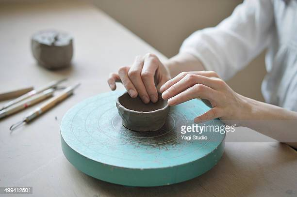 Female potter shaping the vessel manually