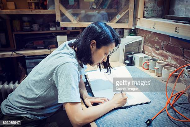 Female potter sketches in studio