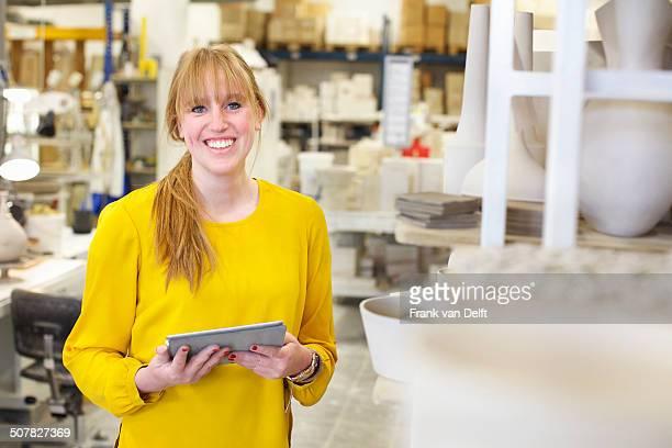 Female potter using digital tablet in ceramic workshop
