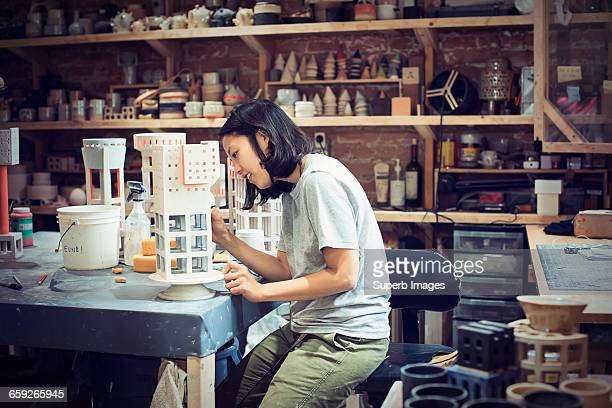 Female potter works in studio