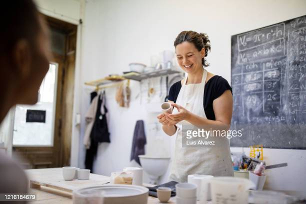 female pottery artists making porcelain pots in art studio - potter stock pictures, royalty-free photos & images