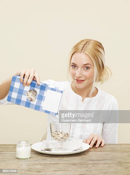 female pouring healthy cereal into a bowl