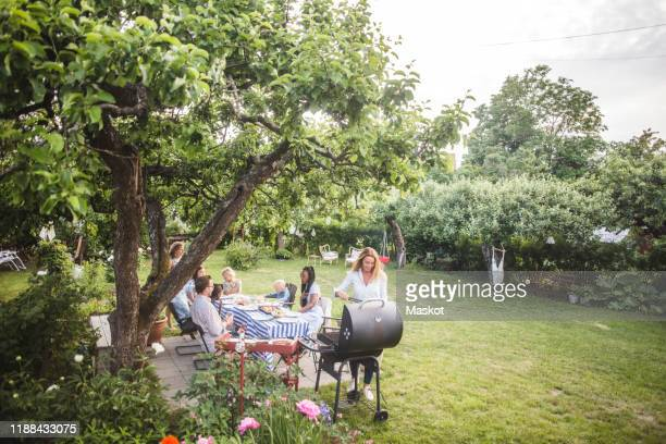 female preparing food o barbecue while family sitting by table in backyard - barbecue social gathering stock pictures, royalty-free photos & images