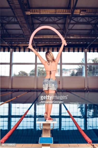 女性の屋内スイミング プールで水中エアロビクスのクラスのための準備