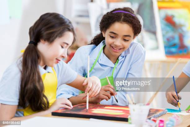 Female preteen friends paint together in art class