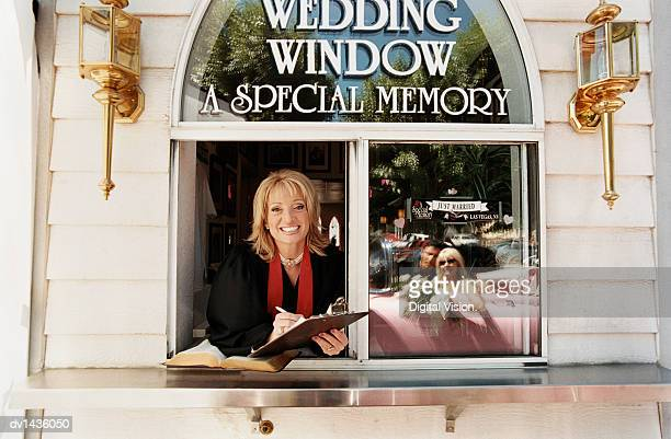 female priest looking out of the window at a drive-in church in las vegas. newlywed couple reflected in the window. - drive through stock pictures, royalty-free photos & images