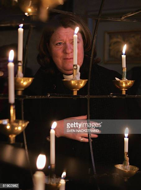 A female priest stands in a moment of grief as she lights a candle for the tidal wave victims in Stockholm's cathedral Storkyrkan 30 December 2004...