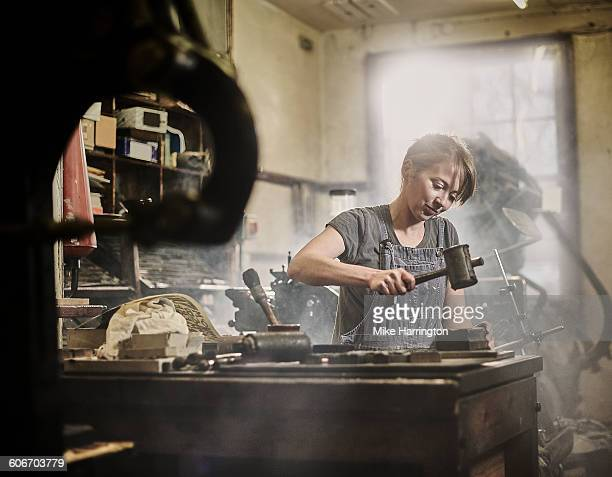 female printer working in letterpress factory - mallet hand tool stock pictures, royalty-free photos & images