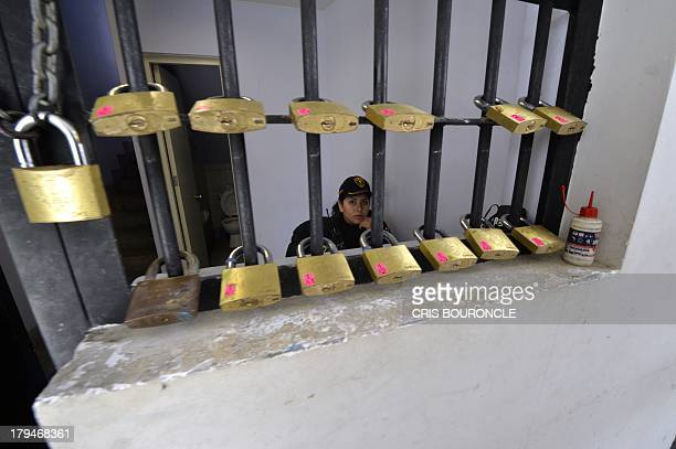 A female prison guard sits in a security cage with door locks ready to be used at the Ancon 2 prison part of the Piedras Gordas Model Penitentiary...