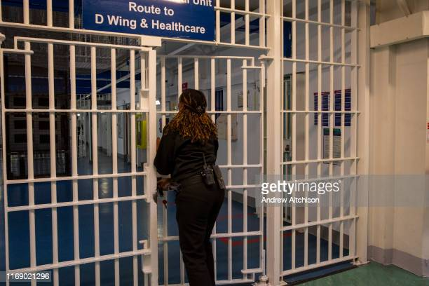 A female Prison Officer locks the metal gate entrance to D Wing and Healthcare Wing of Her Majestys Prison Pentonville London United Kingdom