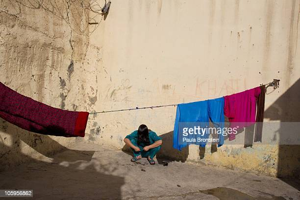A female prisoner combs her hair after washing it in the courtyard of the women's prison October 22 2010 in MazareSharif Afghanistan According to...