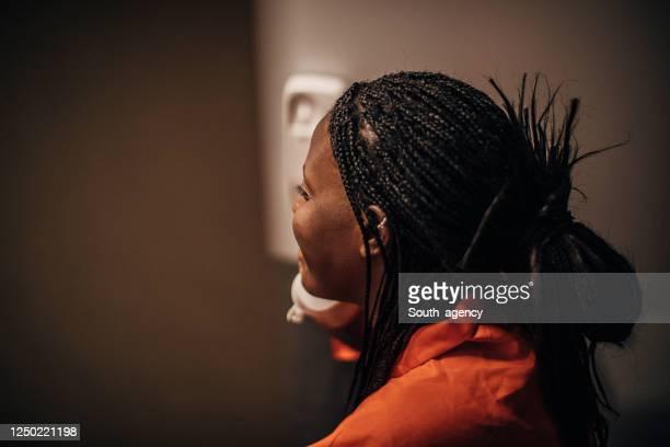 female prisoner talking on phone in prison visit room - prisoner stock pictures, royalty-free photos & images