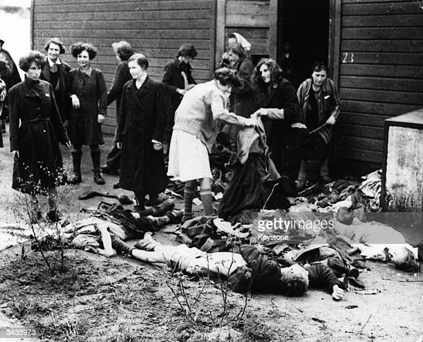 Female prisoners removing the clothing from corpses at Belsen concentration camp to be burnt as fuel Germany April 20 1945
