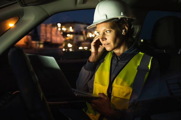 Female professional adjusting in-ear headphones holding laptop in car