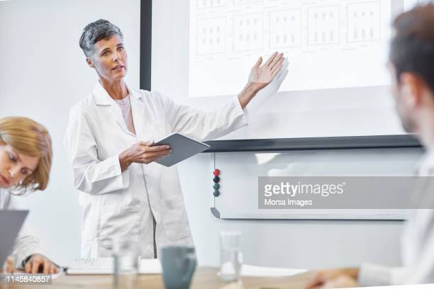 female professional discussing over treatment - mid adult women stock pictures, royalty-free photos & images