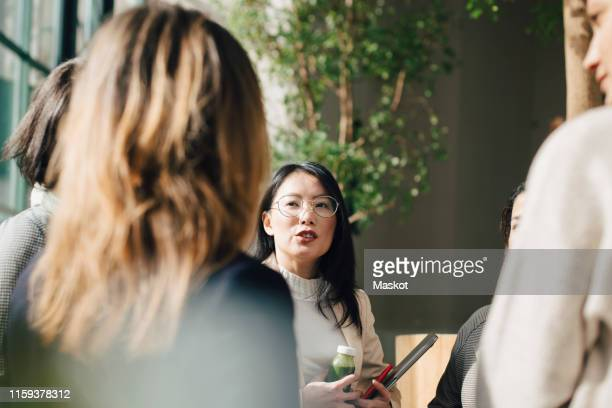 female professional discussing with coworkers in meeting at conference event - businesswear stock pictures, royalty-free photos & images